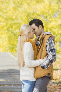 A woman about to kiss her boyfriend in the park
