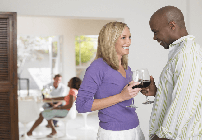 a man and a woman liking a glass of wine together