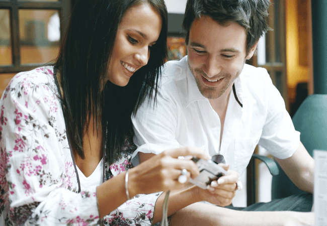 a man and a woman looking at pictures together and enjoying each others company