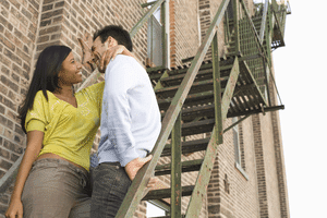 a woman on the stairs with her arm round a man's neck trying to kiss him