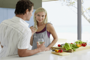 a man and woman flirting in the kitchen while drinking a glass of wine