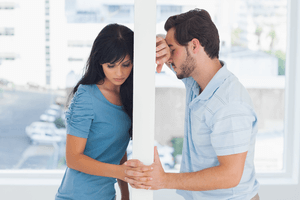 a sad man and woman leaning up against a wall