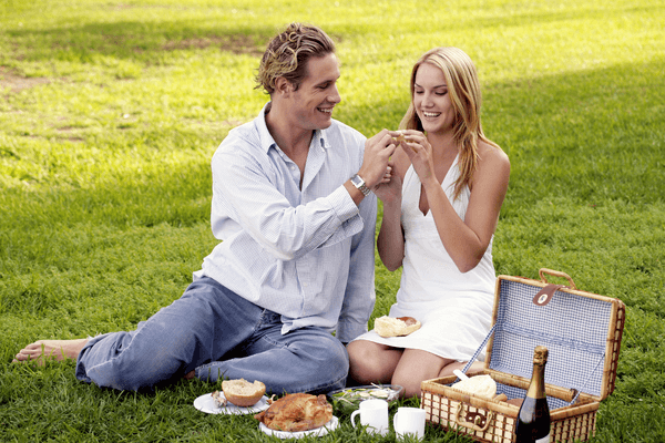 two lovers sharing a picnic together in the park