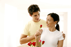 a man offering flowers to his girlfriend to show his love and commitment