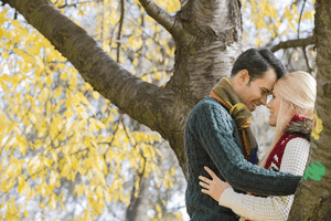 a couple in love hugging by a tree