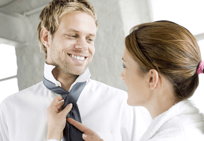 a woman in a relationship with her boyfriend helping him with his tie