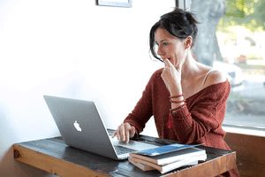 a woman sitting at her computer thinking how to attract a Scorpio man online