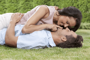a young couple laying on the grass