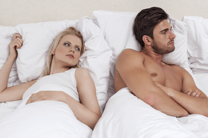 an angry man in bed with his girlfriend