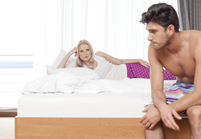 a man and woman in bed not happy