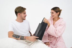a woman giving a man a gift