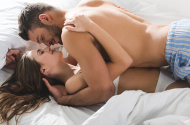 a woman on the bed with her boyfriend making him happy