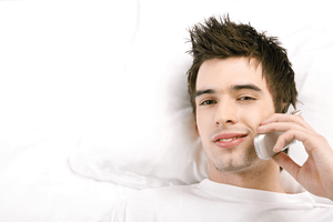 a man seductively talking to a woman on the phone while laying in bed