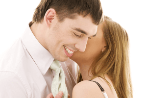 a woman whispering in the ear of her boyfriend as she discovers how to get a scorpio man to commit